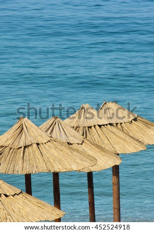 Straw sunshades on an empty beach with turquoise water in the background