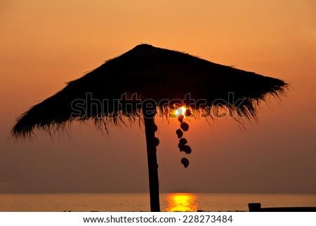 Straw Umbrella in the Sunset - stock photo