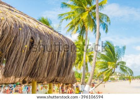 Straw umbrella in the tropical beach of Maragogi, Alagoas, Brazil. - stock photo