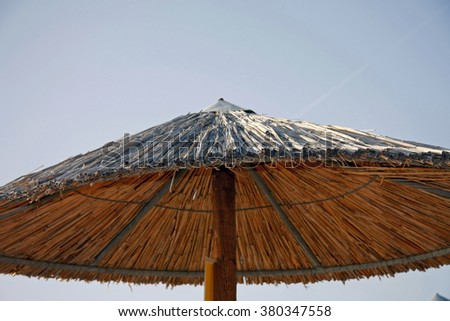 Straw umbrella on the beach  - stock photo
