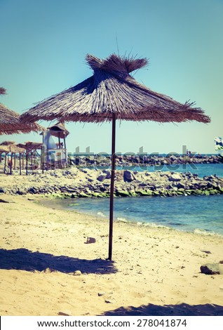 Straw umbrella on the calm blue sea background on a clear sunny day. Shallow depth of field. Selective focus on the parasol. Photo in vintage style. - stock photo