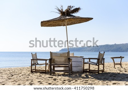 Straw umbrella with chairs on the sand on the beach - early morning, no people, just sun, sky and sea - perfect vacation