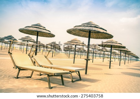 Straw umbrellas and sunbeds at Rimini beach in Italy - Top destination in Emilia Romagna adriatic coast - Vintage filtered look of the world famous italian Riviera with tilted horizon composition - stock photo
