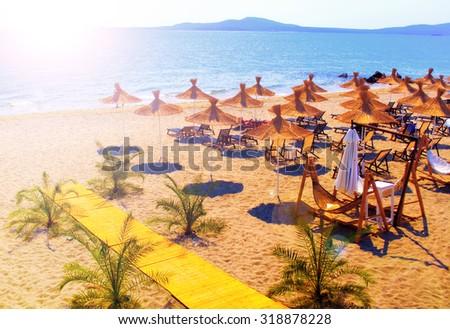 Straw umbrellas on beautiful sunny beach in Bulgaria resort - stock photo