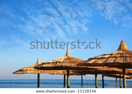 straw umbrellas on blue sky and sea with pier - stock photo