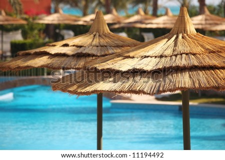 straw umbrellas on blue water - stock photo
