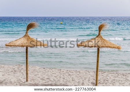 Straw umbrellas on sand beach and clear sky. - stock photo
