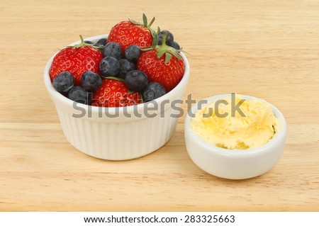 Strawberries and blueberries with clotted cream in a ramekin on a wooden board