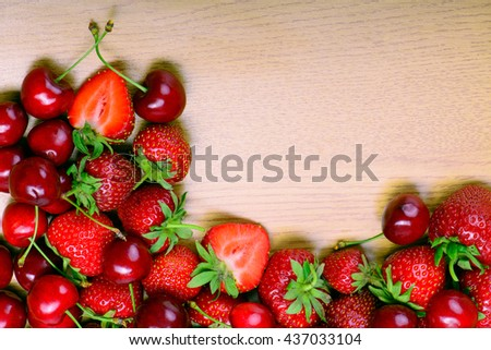 Strawberries and cherry on wooden cutting board  - stock photo