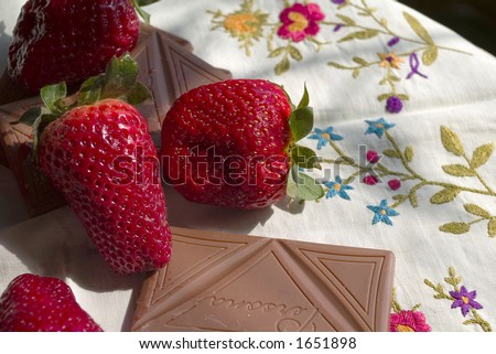 strawberries and chocolate bar on table-cloth with embroidery