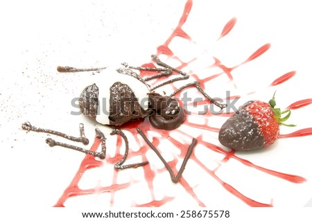Strawberries and chocolate dessert in the form of a spider on a white background