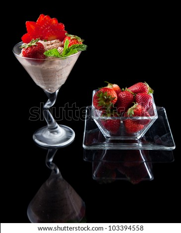 strawberries and chocolate mousse in a chilled martini glass with fresh mint garnish - stock photo