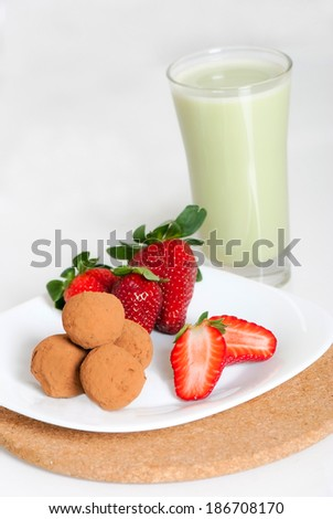 Strawberries and chocolate truffles on a white plate