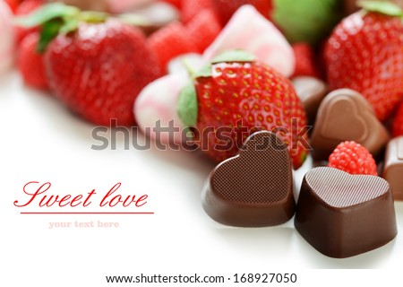 strawberries and chocolates on white background - stock photo