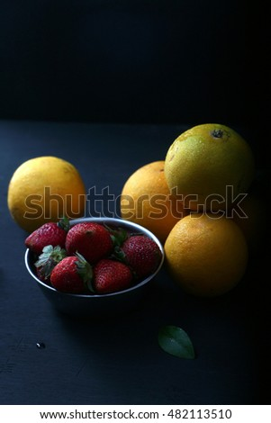 Strawberries and oranges on dark background.