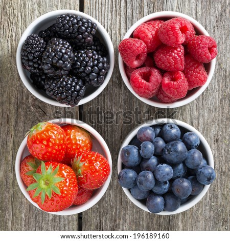 strawberries, blueberries, blackberries and raspberries in bowls, top view, close-up - stock photo