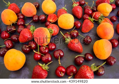 Strawberries, cherries, apricots on a dark background