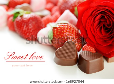 strawberries, chocolates and rose on white background - stock photo
