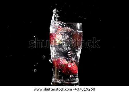 Strawberries falling in glass of water and cause spray
