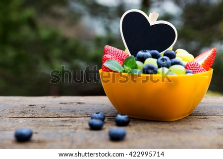 strawberries, grapes and blueberries on wooden table, black heart with copyspace - stock photo