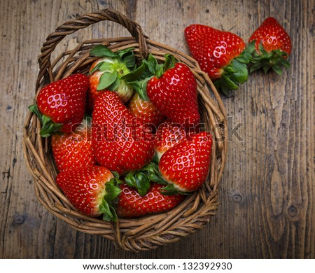 strawberries in a basket - wooden  background - stock photo