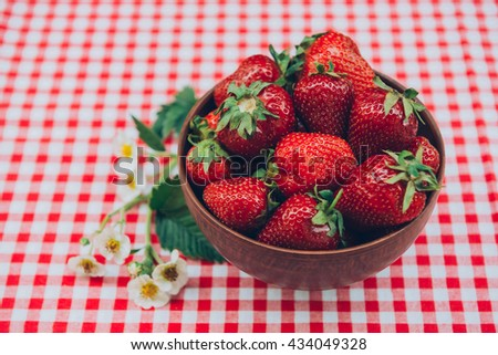 Strawberries in a bowl and milk on the table with wooden background