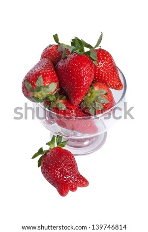 Strawberries in a bowl isolated on white background.  One is next to the cup.