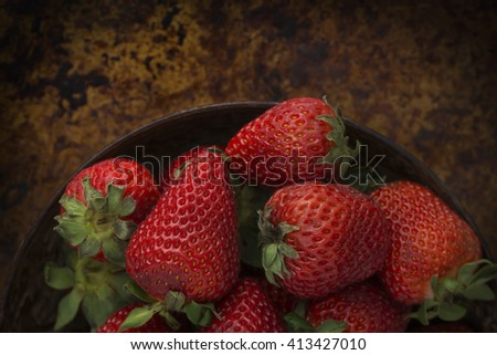 Strawberries in a bowl on a rustic background