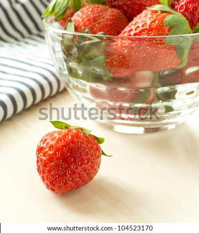 Strawberries in a glass on the table - stock photo