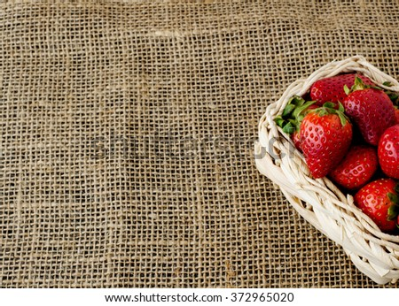 Strawberries in a small basket on the beige jute table cloth - stock photo