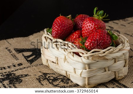 Strawberries in a small basket on the jute table cloth - stock photo