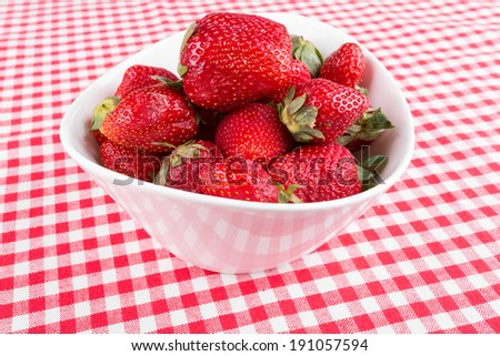 strawberries in a white bowl on a tablecloth