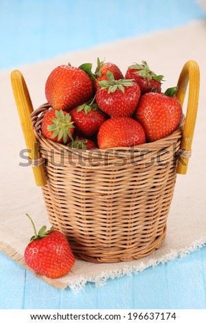 strawberries in a wicker basket on a wooden boards painted
