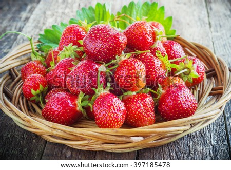 strawberries in a wicker basket on old wooden background - stock photo