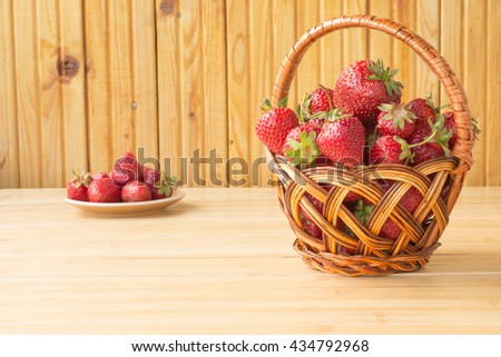 Strawberries in a wicker  bucket on a wooden surface