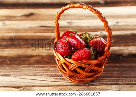 Strawberries in basket on brown wooden background