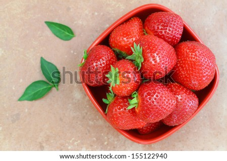 Strawberries in bowl on terracotta surface  - stock photo