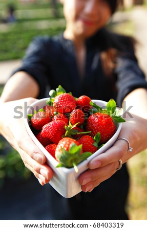 strawberries in heart shape bowl show by girl - stock photo