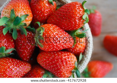 strawberries in small sack on wooden table background