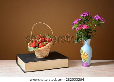 Strawberries in wicker baskets and flowers in a vase on the table - stock photo
