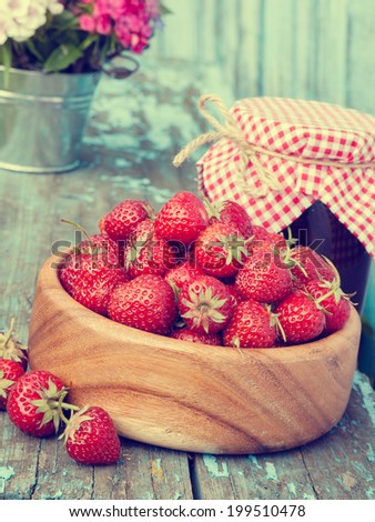 strawberries in wooden bowl and jam on wooden plank in vintage tones. - stock photo
