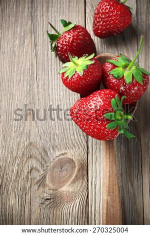 Strawberries in wooden spoon on weathered wood. - stock photo