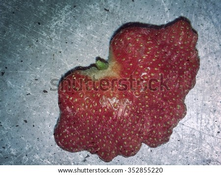 Strawberries mutant on textured background - stock photo