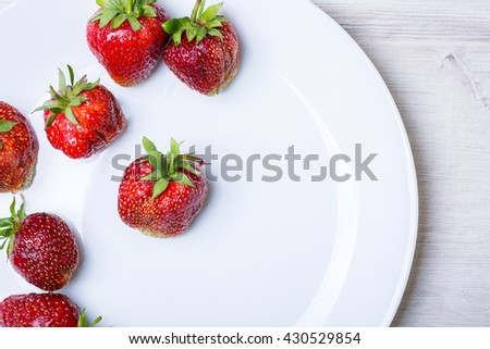 strawberries on a plate on wooden background with copy space