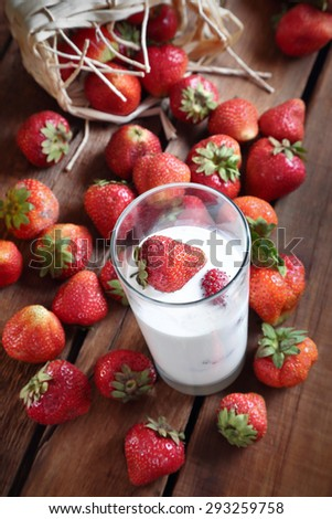 strawberries on a wooden table and a glass with whipped cream and strawberries - stock photo