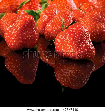 Strawberries on black glossy table - stock photo