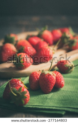Strawberries on wood background in vintage style with film filter effect