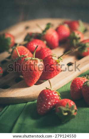 Strawberries on wood background in vintage style with film filter effect - stock photo