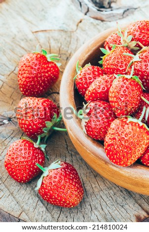 Strawberries. Organic Berries Closeup. Ripe Strawberry In The Fruit Garden, Old Wooden Bowl Filled With Succulent Juicy Fresh Ripe Red Strawberries On An Old Birch Stump. Toned Image - stock photo
