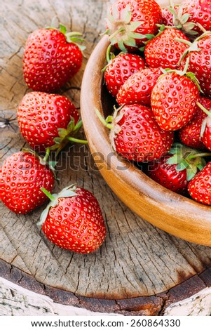 Strawberries. Organic Berries Closeup. Ripe Strawberry In The Fruit Garden, Old Wooden Bowl Filled With Succulent Juicy Fresh Ripe Red Strawberries On An Old Birch Stump. Toned Instant Image - stock photo
